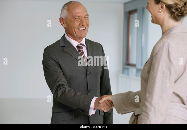 Elderly manager and business woman shaking hands, in high spirits - Stock Image