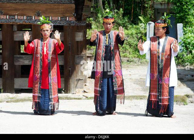 Three Batak tribeswomen in tribal costume performing traditional dance, Huta Bolon, Simanindo, Sumatra, Indonesia - Stock Image