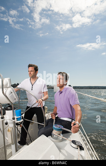 Two men sailing a boat - Stock Image