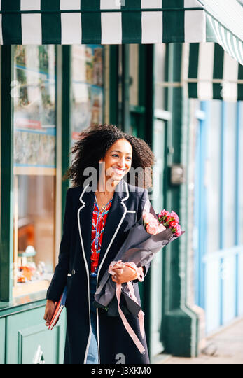 Stylish woman strolling along street with bunch of flowers - Stock Image