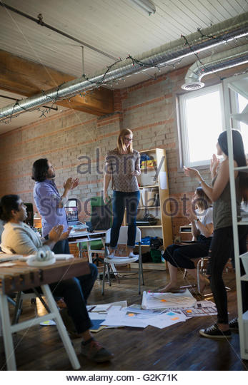 Coworkers clapping for designer standing on chair in office - Stock Image