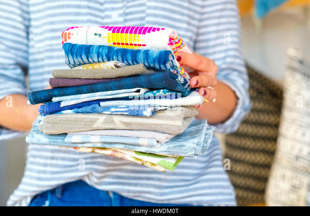 Mid section of female interior designer holding stack of textile swatches in retail studio - Stock-Bilder