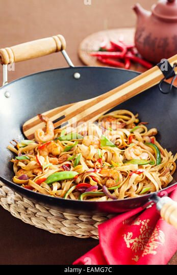 Asian stir fried noodle with vegetabled and prawns in wok - Stock Image