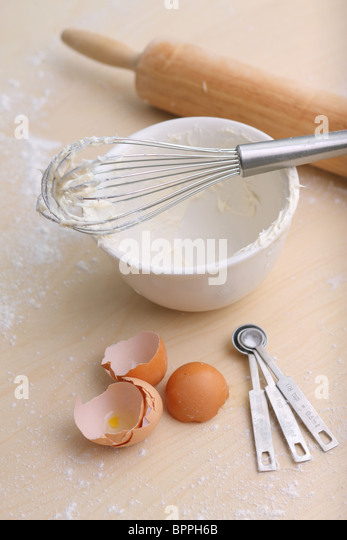 Baking; Whisk, bowl, measuring spoons, egg shells and rolling pin - Stock Image