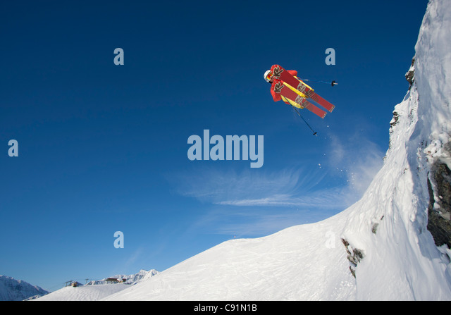 Downhill skier makes an extreme jump from a ledge while skiing at Alyeska Resort, Southcentral Alaska, Winter - Stock Image