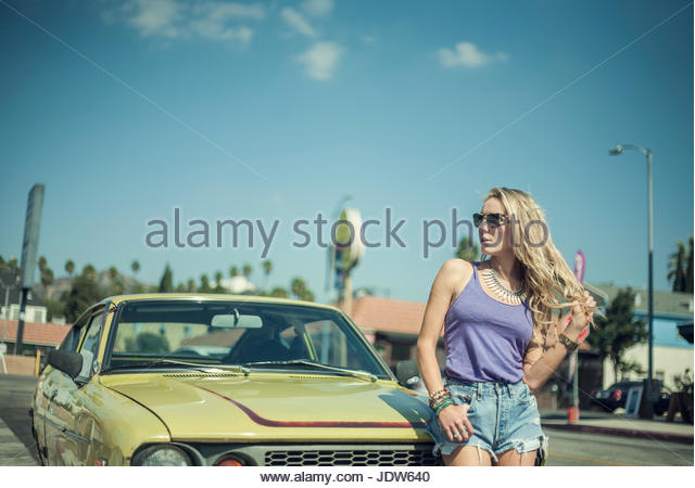 Young woman leaning against car - Stock-Bilder