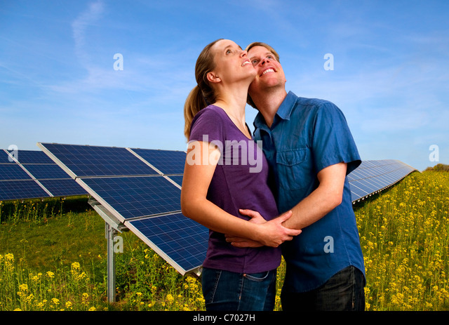 Couple hugging by solar panels - Stock Image