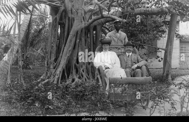 A mature Caucasian woman with a neutral expression and a smiling mature Caucasian man sit in front of trees and - Stock Image