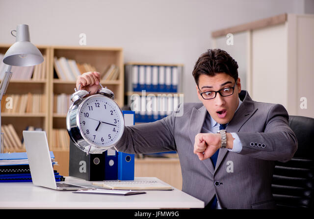 Businessman with clock failing to meet deadlines - Stock Image