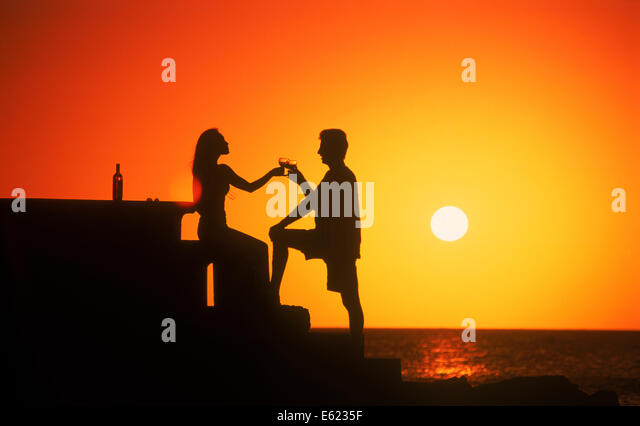 Couple toasting life and love at sunset Uruguay - Stock Image