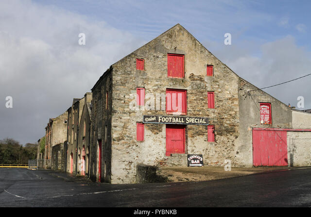 Old store building on the quayside at Ramelton County Donegal. 'Football Special' is a non-alcoholic drink - Stock Image