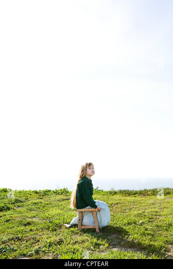Girl sitting alone in field under bright sky - Stock Image