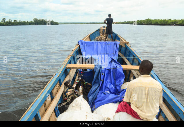 Small wooden boat carrying people and goods from Cabinda to Angola around DR Congo - Stock-Bilder
