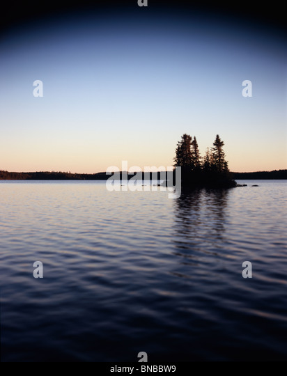 Silhouette of trees on an island in a lake- select focus image - Stock Image