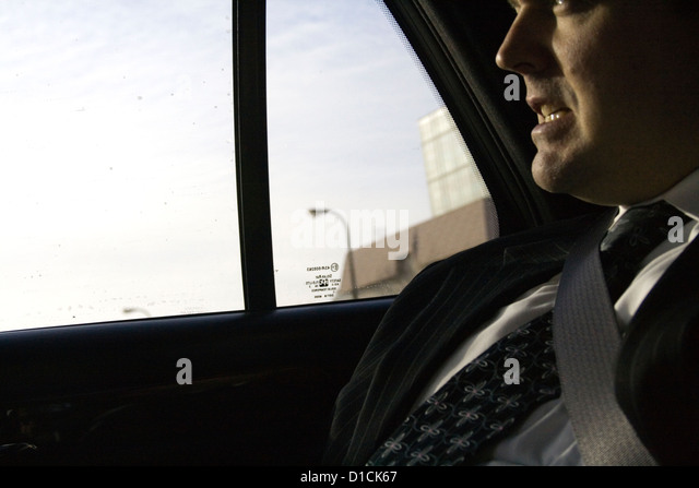 Tense businessman age 38 riding to an important business meeting and luncheon. Minneapolis Minnesota MN USA - Stock Image