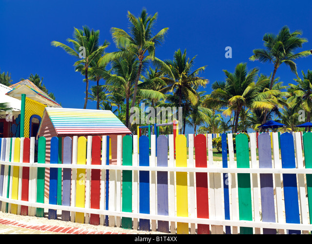 Dominican Republic Punta Cana Bavaro Beach multi colored picket fence and palm trees - Stock-Bilder