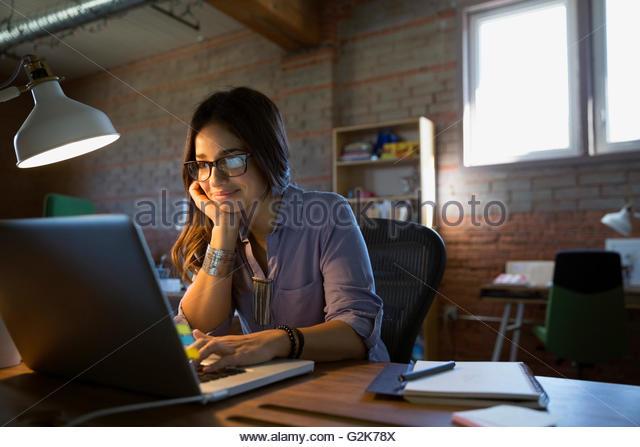 Female designer using laptop at desk in office - Stock Image