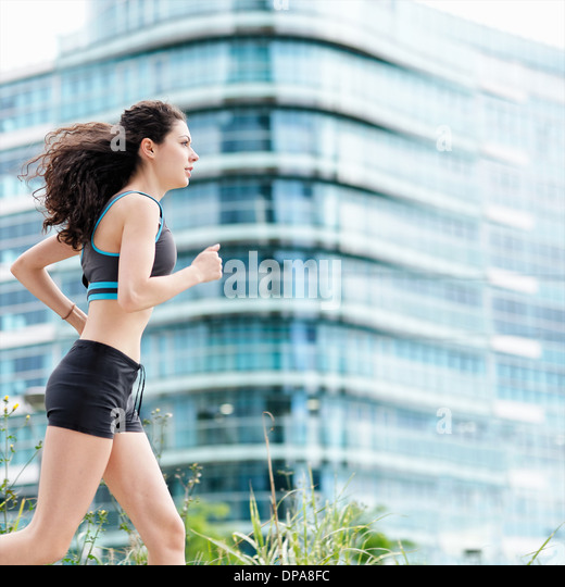 Young woman running in city - Stock-Bilder