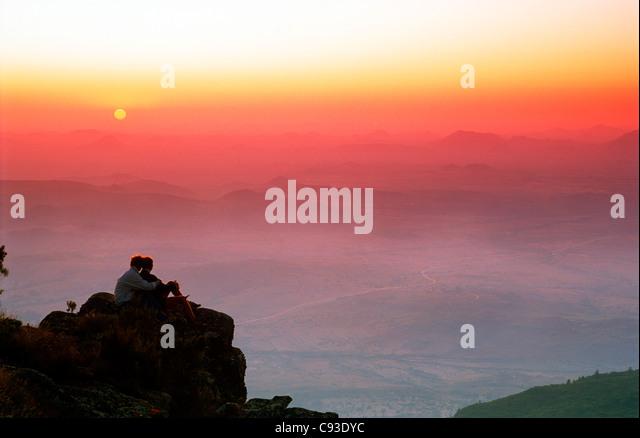 Couple overlooking plains from Eastern Highlands of  Zimbabwe at sunset - Stock Image