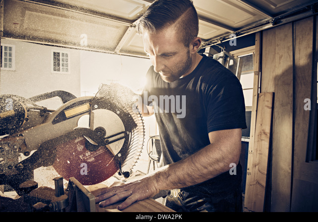 Male carpenter sawing plank of wood in workshop - Stock Image