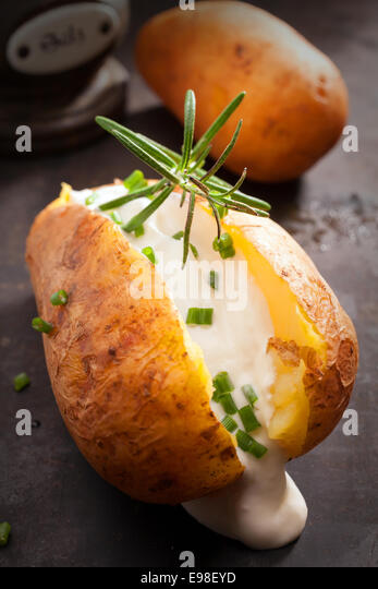 Sliced baked jacket potato cooked over a summer BBQ in foil with sour cream and chopped chives topped with rosemary - Stock Image
