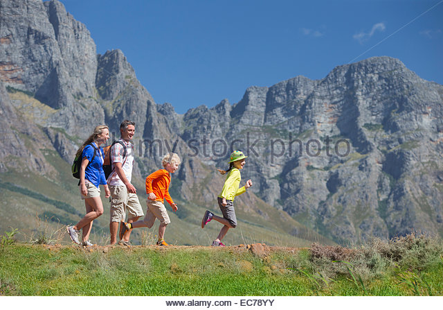 Multi generation family hiking on mountain path - Stock-Bilder