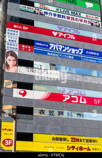 Facade of a Japanese building covered in advertising billboards. - Stock Image