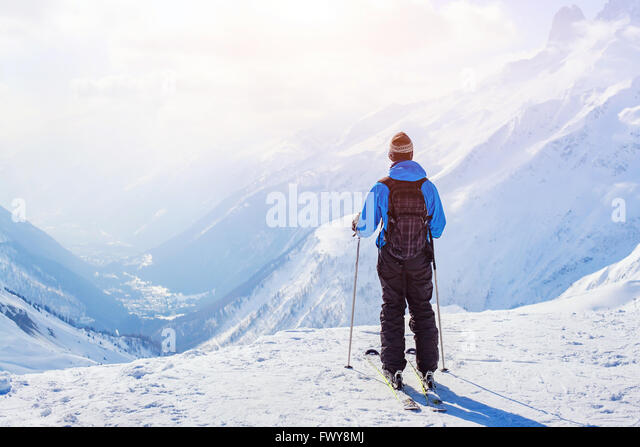 skiing in Alps, skier on beautiful mountain background at sunset - Stock Image