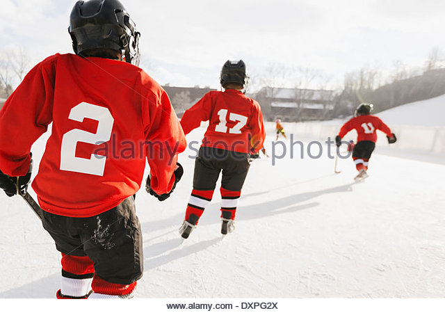 Rear view of ice hockey players training on rink - Stock Image
