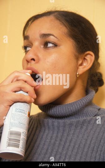 girl spraying aerosol under her tongue - Stock Image