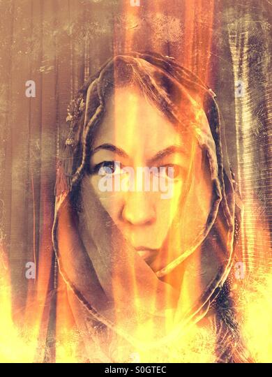 Woman with hood in flames - Stock Image