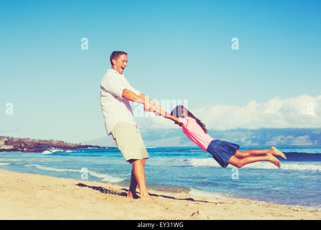 Happy father and daughter playing together at the beach. Fun vacation summer lifestyle. - Stock Image