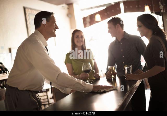 Friends enjoying a drink in wine bar - Stock-Bilder