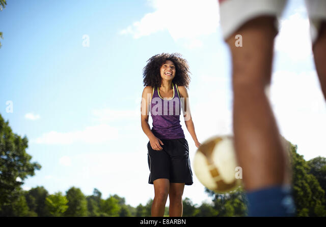 Young couple playing football in park - Stock Image
