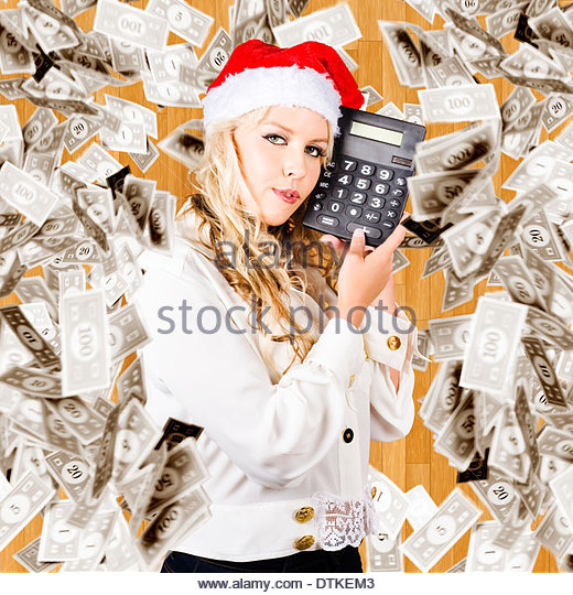 Christmas Woman In Santa Hat Holding Dollars Calculator Underneath Falling Banknotes In A Financial Cost Of Christmas - Stock Image