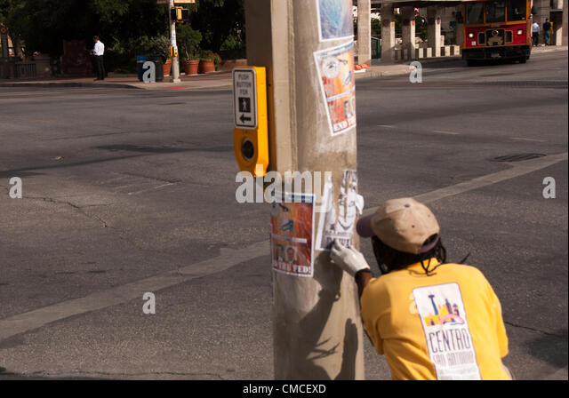 17 July 2012 San Antonio, Texas, USA - Centro San Antonio worker removes anti-Obama signs from a street  light in - Stock Image