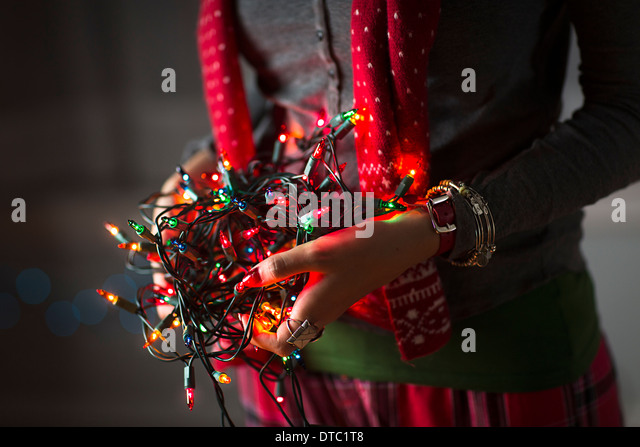 Close up of young woman holding tangle of christmas lights - Stock Image