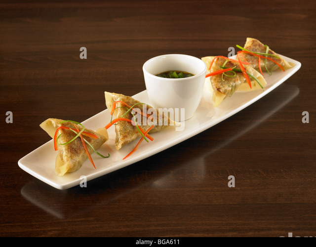 Pan fried dumplings with dipping sauce - Stock Image