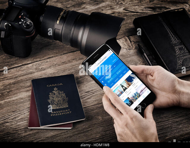 Woman hands with Apple iPhone 7 displaying flight information on a table with passports, a camera and a notebook, - Stock Image