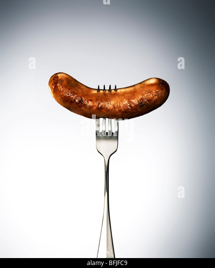 suasage on a fork - Stock Image