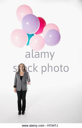 Businesswoman holding bunch of multicolor balloons against white background - Stock-Bilder