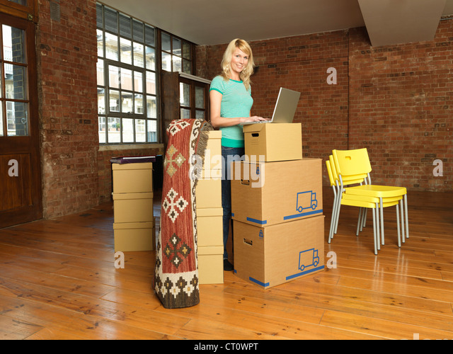 Woman with cardboard boxes in new home - Stock Image