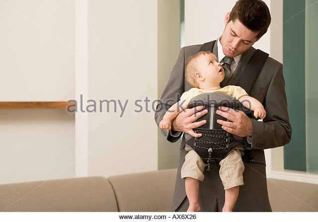 Businessman with his son in baby carrier - Stock Image