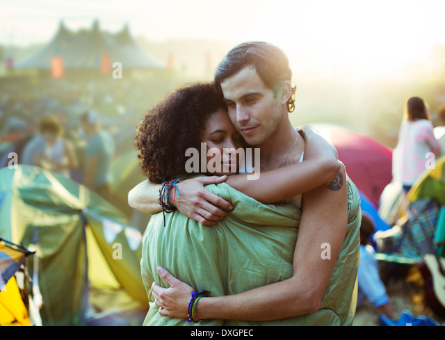Couple in sleeping bag hugging outside tents at music festival - Stock Image