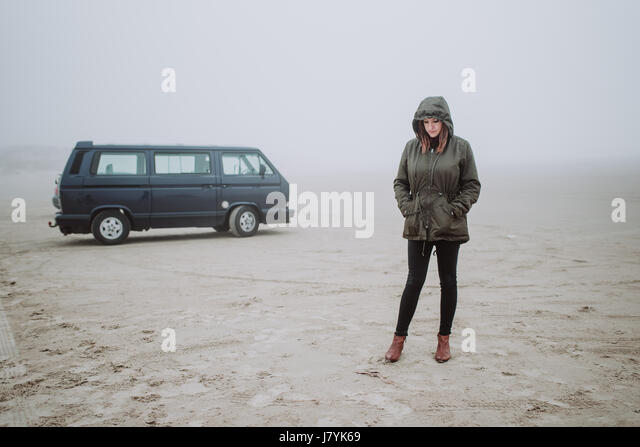 Woman standing in front of her van on an empty beach in winter time - Stock Image