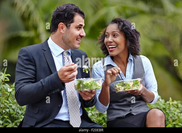 Business people sitting side by side enjoying a salad on lunch break, face to face, smiling - Stock Image