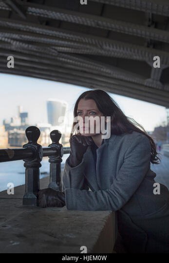 Attractive dark haired woman looking tense and anxious looks out from under a bridge in an urban setting - Stock Image