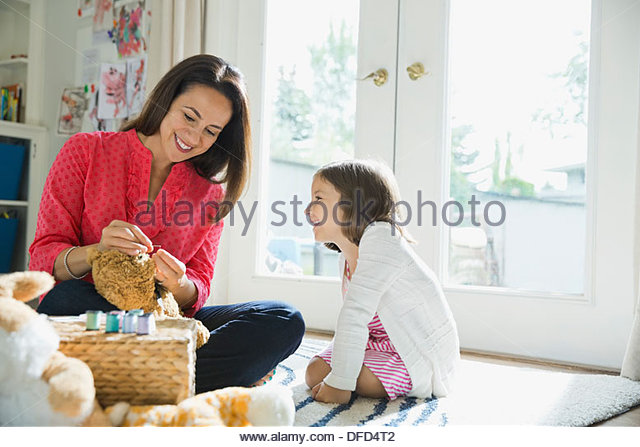 Mother and daughter sewing stuffed animals - Stock Image