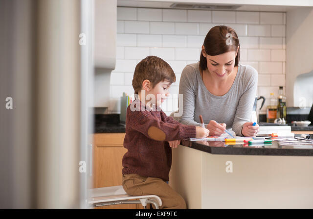 Mother and son drawing together in kitchen - Stock-Bilder