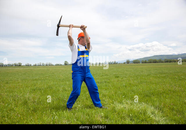 Worker with pick axe is digging on a wide green field. - Stock Image